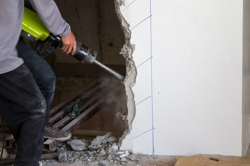 Worker using a jackhammer to drill into wall. professional worker in construction site