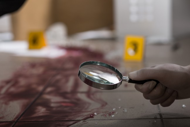 Forensic scientist looking blood through magnifying glass