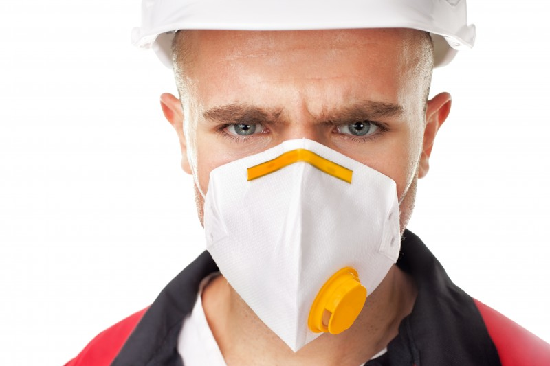 Closeup portrait of serious worker wearing respirator and white helmet isolated on white background